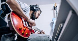 Junger Mann zuhause beim Gitarre Spielen - Powersoak oder Kopfhörer